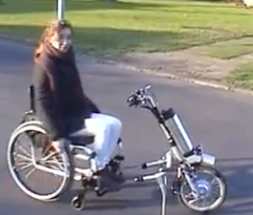 Woman sitting in a non motorized wheelchair with a single wheel and handlebars in front.